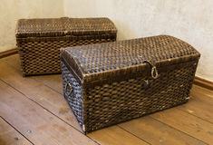 Two old wicker from cane chests standing in the room corner Stock Image