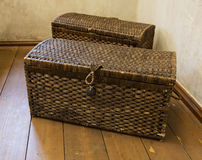 Two old wicker from cane chests standing in the room corner Royalty Free Stock Photos