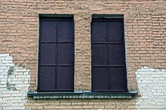 Two old windows covered with brown iron on a brick wall Royalty Free Stock Photos