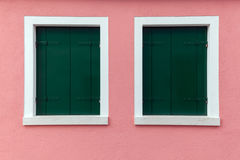Two old windows with dark green shutters on light pink wall. Picturesque two old windows with dark green shutters on light pink wall (Burano island, Venice Royalty Free Stock Photography