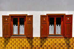 Two old windows with opened shutters on white wall and yellow ti Royalty Free Stock Images