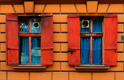 Two old windows  with red shutters in the stone wall with blue curtains Stock Photography