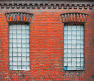 Two old windows with square glass blocks in old worn down factory building royalty free stock photo