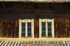 Two old windows on wooden house Royalty Free Stock Image
