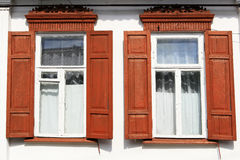 Two  windows with wooden red shutters. Two old windows with wooden red shutters Royalty Free Stock Images