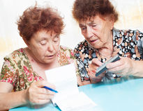 Two old women consider receipts Stock Image
