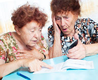 Two old women consider receipts Stock Photo