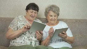 Two old women holding the silver digital tablets. Two old women sitting on a beige sofa at home. Each old woman holds the silver digital tablet stock video footage