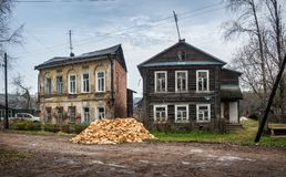 Two old wooden houses. And a pile of firewood in the town of Vyshny Volochyok on a rainy day royalty free stock photo