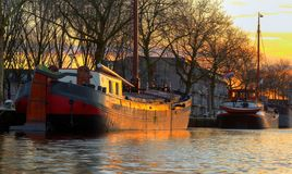 Two old wooden ship in sunset light in the river canal by the sh stock images