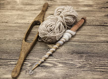Two old wooden spindle with a ball of wool thread for the manufacture of woolen threads on a wooden background Stock Photos