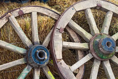 Two old wooden wagon wheels lean on hay stacks Stock Image