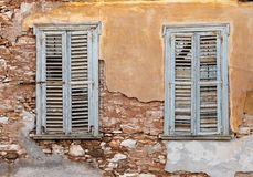 Two old wooden windows on grunge weathered wall. Two old wooden windows with shutters, on grunge weathered wall stock photography