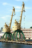 Two old yellow harbor crane Stock Images