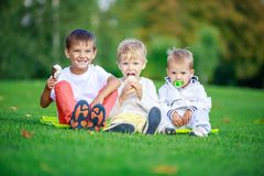 Two boys eating ice cream, youngest brother sucking pacifier Stock Photo