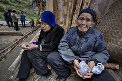 Two older farmer Asians, rural women, sitting near peasant house Royalty Free Stock Image