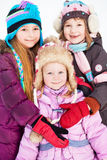 Two older girls embrace younger girl standing in winter park Stock Photo
