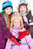 Two older girls embrace younger girl standing in winter park. Focus on little girl Stock Photo