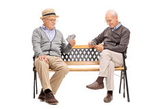 Two older men playing cards seated on a bench. Studio shot of two older men playing cards seated on a wooden bench isolated on white background Royalty Free Stock Photo