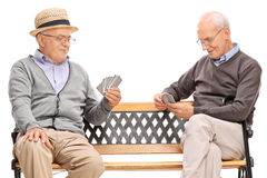 Two older men playing cards seated on a bench Royalty Free Stock Photos