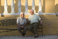 Two older men talk on bench of village of Southern Spain off highway A49 west of Sevilla Stock Image