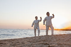 Two older people practicing Taijiquan on the beach at sunset, China royalty free stock photos