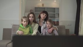 Two older sisters with sad faces and a younger sister and brother sitting on the couch in the guest room and watch TV stock video footage