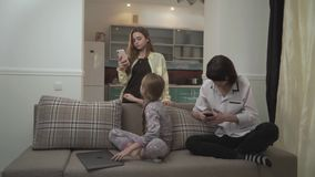 Two older sisters texting messages on cell phones younger girl typing on laptop sitting on the couch in the room. Little stock footage