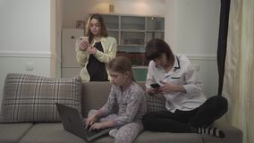 Two older sisters texting messages on cell phones younger girl typing on laptop sitting on the couch in the room. Family stock video