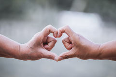 Two older women making heart shape with hands together Stock Photos