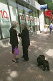 Two older women pause for a moment of talk on the streets of Madrid, Spain Stock Photo