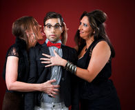 Two older women with a shy young man. Two aggressive cougar women corner a shy young man Royalty Free Stock Images