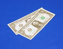 Two one dollar bills at an angle. Two new one dollar notes at an angle against a blue background Royalty Free Stock Photography