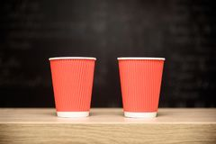 Two one-time paper cups for coffee, wooden bar counter, dark soft background with highlighting center and copy space, design templ. Two one-time paper cups for Royalty Free Stock Images