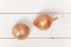 Two onions on wooden table Royalty Free Stock Images