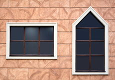Two opaque windows with dark glass on the stones wall. The frame of one of them has an acute angle. Beautiful unusual windows Royalty Free Stock Photos