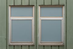 Two opaque windows on green wall. Two opaque worn warehouse windows on green wall stock photos
