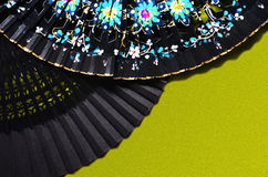Two open hand fan. On a green background Stock Photos