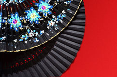 Two open hand fan on the red background. Two open hand fan with an ornament on a red background Royalty Free Stock Images