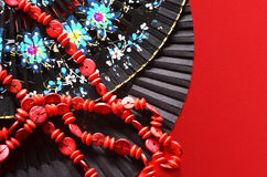 Two open hand fan and red beads. Two open hand fan and beads on red background Royalty Free Stock Photo