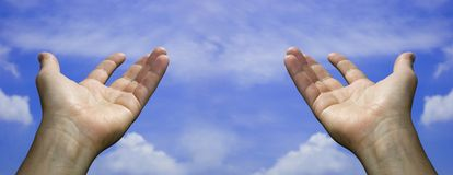 Two open hands in the sky Royalty Free Stock Photo