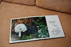 Two open pages of wedding book on sofa. stock images