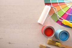 Two open paint cans and tools on wooden table top stock images