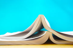 Two opened books in blue background. In the image, there are two opened books. They are on a wooden table and they are in the blue background stock photos