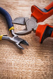 Two opened nippers close up on wooden board Royalty Free Stock Photos