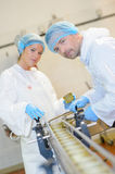 Two operatives working on conveyor line Stock Images