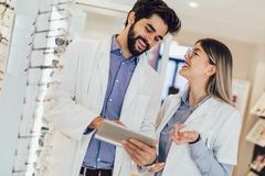 Two ophthalmologists using digital tablet in an optical store stock image