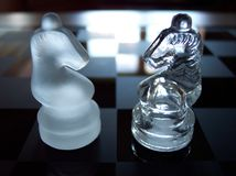 Two Opposing Chess Knights. Two knights facing off on a glass chessboard with light streaming in Stock Photo