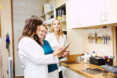Two opticians showing customer options royalty free stock image