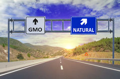 Two options GMO and Natural on road signs on highway. Close Royalty Free Stock Photos